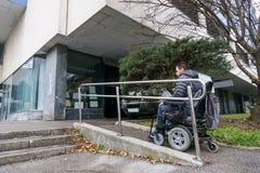 Homme dans un fauteuil roulant utilisant une rampe à côté des escaliers images libres de droits