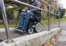 Homme dans un fauteuil roulant utilisant une rampe à côté des escaliers photographie stock