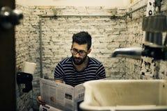 Homme dans un journal de lecture de toilettes photos stock