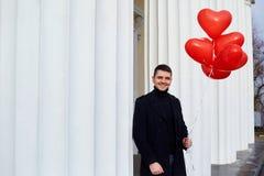 Homme dans un manteau avec les coeurs rouges de ballons dans des mains Image stock