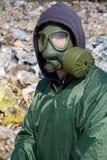 Homme dans un masque de gaz contre la nature polluée photographie stock libre de droits