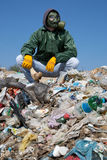 Homme dans un masque de gaz se reposant sur les déchets et tenant un os Photographie stock
