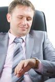 homme dans un procès élégant avec le regard de relation étroite sur la montre Photos libres de droits
