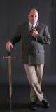 Homme dans un procès d'affaires se penchant sur une épée photos stock
