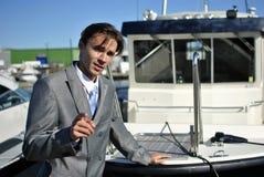 Homme dans un procès gris d'affaires près du yacht Images libres de droits