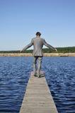Homme dans un procès gris marchant sur le pilier Photo stock