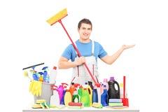 Homme dans un uniforme tenant un balai et posant avec le suppli de nettoyage Photographie stock