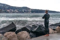 Homme dans un vêtement isothermique, surfer, se tenant sur le rivage et regardant les vagues à l'arrière-plan de la montagne, Sor photos stock