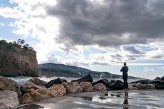 Homme dans un v?tement isothermique, surfer, se tenant sur le rivage et regardant les vagues ? l'arri?re-plan de la montagne, Sor photographie stock