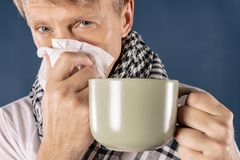 Homme dans une écharpe à carreaux avec la grande tasse et tissu sur le fond bleu Soulagement froid et de grippe de maladie image libre de droits