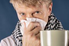 Homme dans une écharpe à carreaux avec la grande tasse et tissu sur le fond bleu Soulagement froid et de grippe de maladie images stock