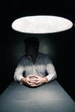 Homme dans une chambre noire illuminée seulement par la lampe Photos libres de droits