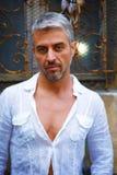 Homme dans une chemise blanche et une fenêtre médiévale ornementale sur le backgrckgroundoun Photos stock