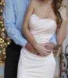 homme dans une chemise bleue et une femme dans une robe - étreignant sur un fond des lumières Images libres de droits