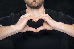 Homme dans une chemise noire montrant le coeur de geste de main Photos stock