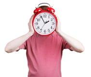 Homme dans une chemise rose avec un réveil photos stock