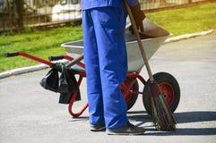 Homme dans une combinaison fonctionnante avec un batteur dans sa main et avec un chariot de déchets Nettoyage d'été dans la ville photographie stock libre de droits