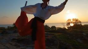 Homme dans une danse ukrainienne de costume de pays sur des échasses à la forteresse en été dans le ralenti banque de vidéos