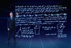 Homme dans une plein-taille de costume écrivant le sort de formules trigonométriques dans le ciel Photo stock
