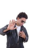 Homme dans une veste en cuir avec des lunettes de soleil montrant l'arrêt Photos stock