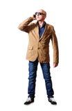 Homme dans une veste et des jeans parlant au téléphone portable Photographie stock libre de droits