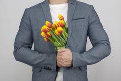 Homme dans une veste tenant un bouquet des tulipes Images stock