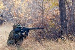 Homme de acroupissement avec une arme à feu Image stock