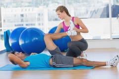 Homme de aide d'entraîneur féminin avec ses exercices au gymnase photos stock
