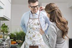 Homme de aide de femme pour mettre dessus le tablier dans la cuisine Image libre de droits