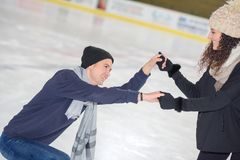 Homme de aide de jeune womann à tenir sur la patinoire Image libre de droits