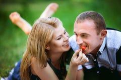 Homme de alimentation de femme une fraise Photo libre de droits