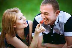 Homme de alimentation de fille une fraise Photo libre de droits