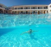 Homme de barbe avec des verres nageant sous l'eau dans la piscine sur un tro Photographie stock