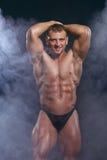 Homme de Bodybuilder avec un corps parfait de muscle sur l'obscurité avec de la fumée Photo libre de droits