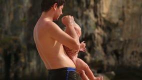 Homme de brune tenant un bébé pleurant banque de vidéos