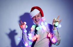 Homme de bureau dans un chapeau rouge de Santa Claus avec les guirlandes colorées Photographie stock libre de droits