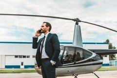 Homme de calme parlant au téléphone tout en se tenant près de l'hélicoptère photographie stock