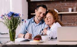 Homme de caresse de femme tout en se reposant dans la cuisine Photographie stock libre de droits