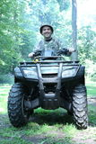 Homme de chasseur conduisant l'atv à quatre roues Images libres de droits