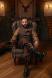 Homme de chasseur s'asseyant dans un whiskey de chaise et de boissons Images stock