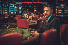 Homme de classe aristocratique derrière la table de jeu dans un casino Image stock