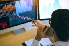 Homme de commerçant d'agent parlant au téléphone et vérifiant des données d'actions d'affaires sur l'ordinateur dans la chambre d photographie stock