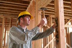 Homme de construction à l'aide du marteau Photos stock