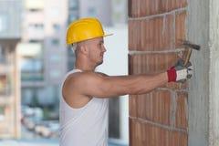 Homme de construction travaillant avec le marteau Photographie stock libre de droits