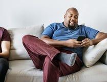 Homme de couleur à l'aide du téléphone portable se reposant avec l'ami Images stock