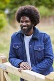 Homme de couleur adulte heureux se penchant sur un fance en bois dans la campagne souriant, fin  images libres de droits