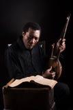 Homme de couleur avec l'instrument de musique ethnique image stock