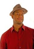 Homme de couleur dans un sourire affecté rouge de chapeau de chemise et de Brown Photo libre de droits