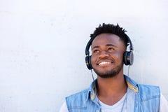 Homme de couleur de sourire écoutant la musique avec des écouteurs Images libres de droits