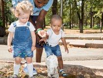 Homme de couleur et groupe d'enfants heureux jouant en parc Image libre de droits